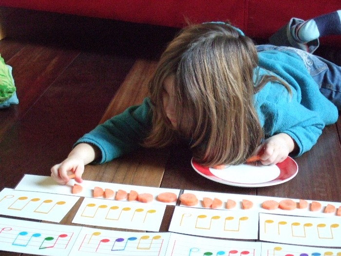 photo, Melianna puts slices of carrot under the song 'zeg eens herder' (tell me shepherd) with rhythm charts