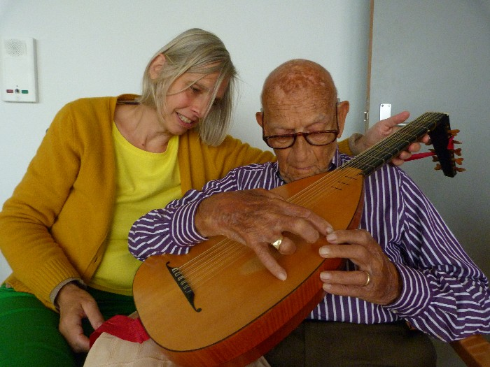 photo, sir Oostrom plucks the lute, Leonoor helps